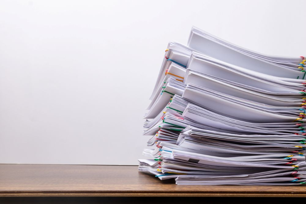 A large stack of papers on a desk that symbolize the importance of a document management solution.