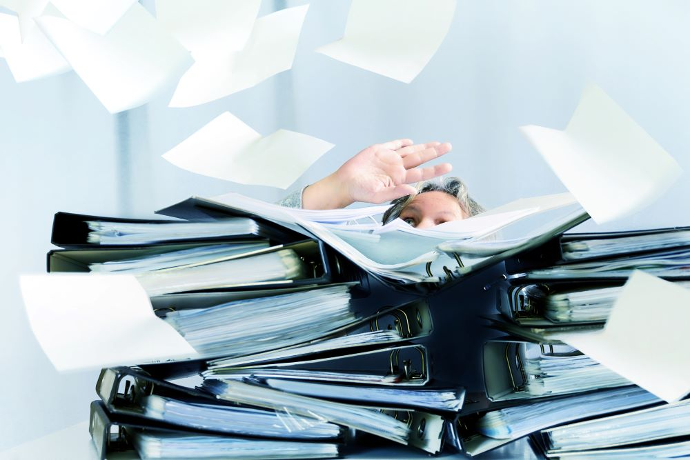 A close up of a businessman drowning in paper files and binders to signify the importance of businesses having a document management solution.